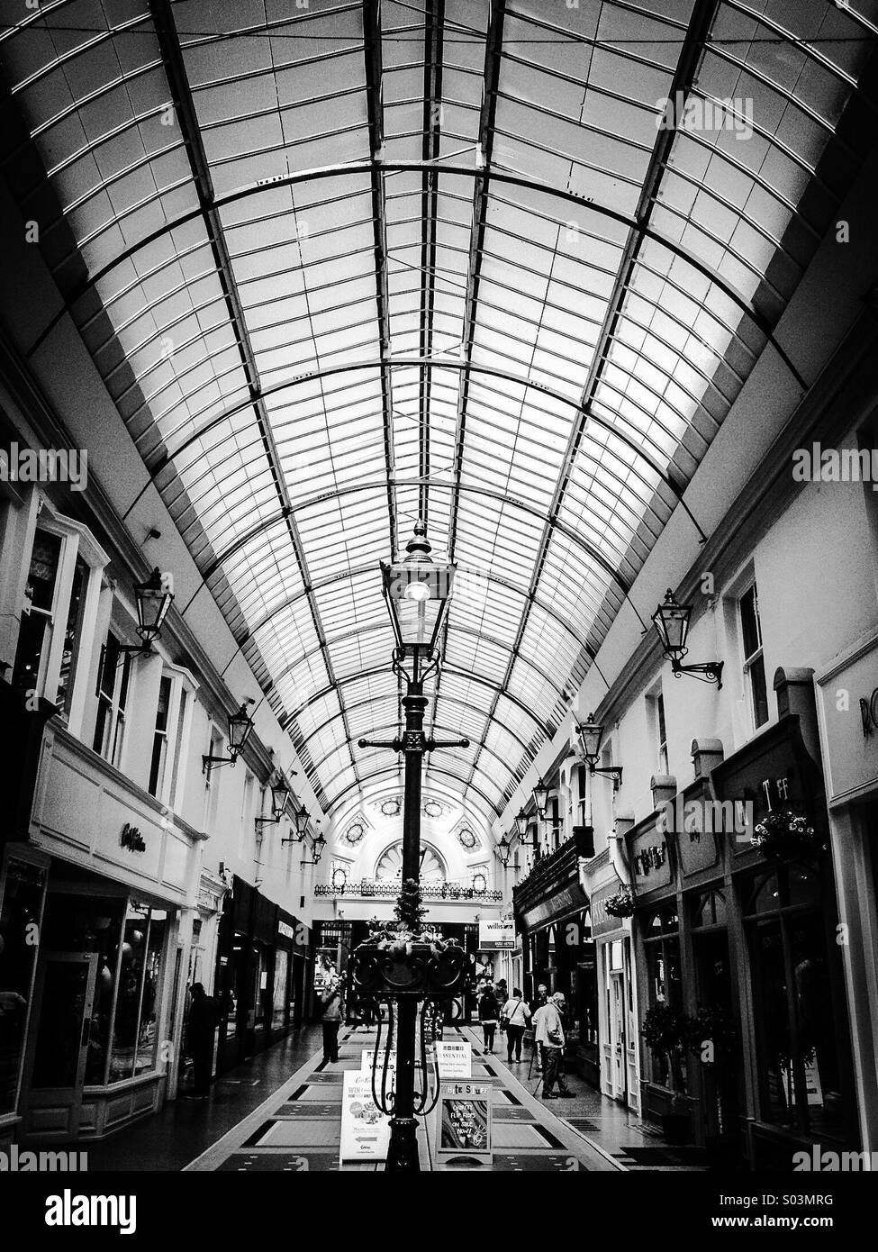 An internal view in mono, of Westbourne Arcade, Bournemouth, showing the covered symmetrical facades of the Grade - Stock Image