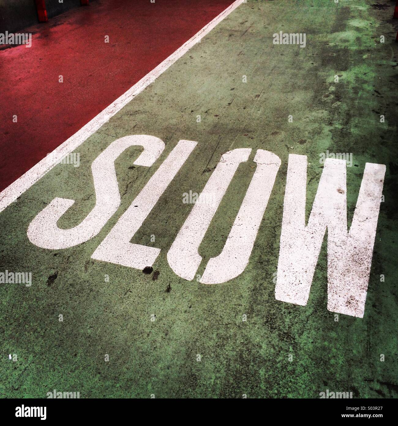 The word slow painted on cycle way - Stock Image