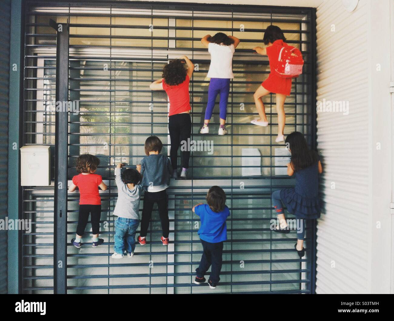 Seven child climbing a wall - Stock Image