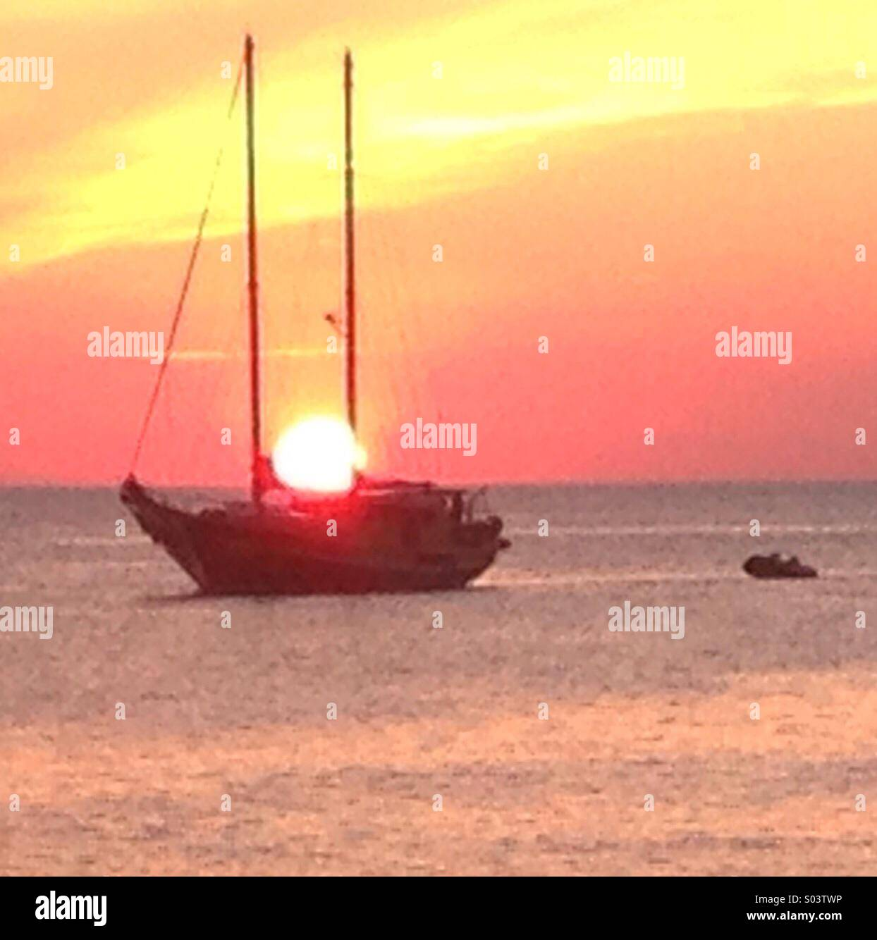 Sunset in Ibiza. Twin masted ship sails into the sunset Stock Photo