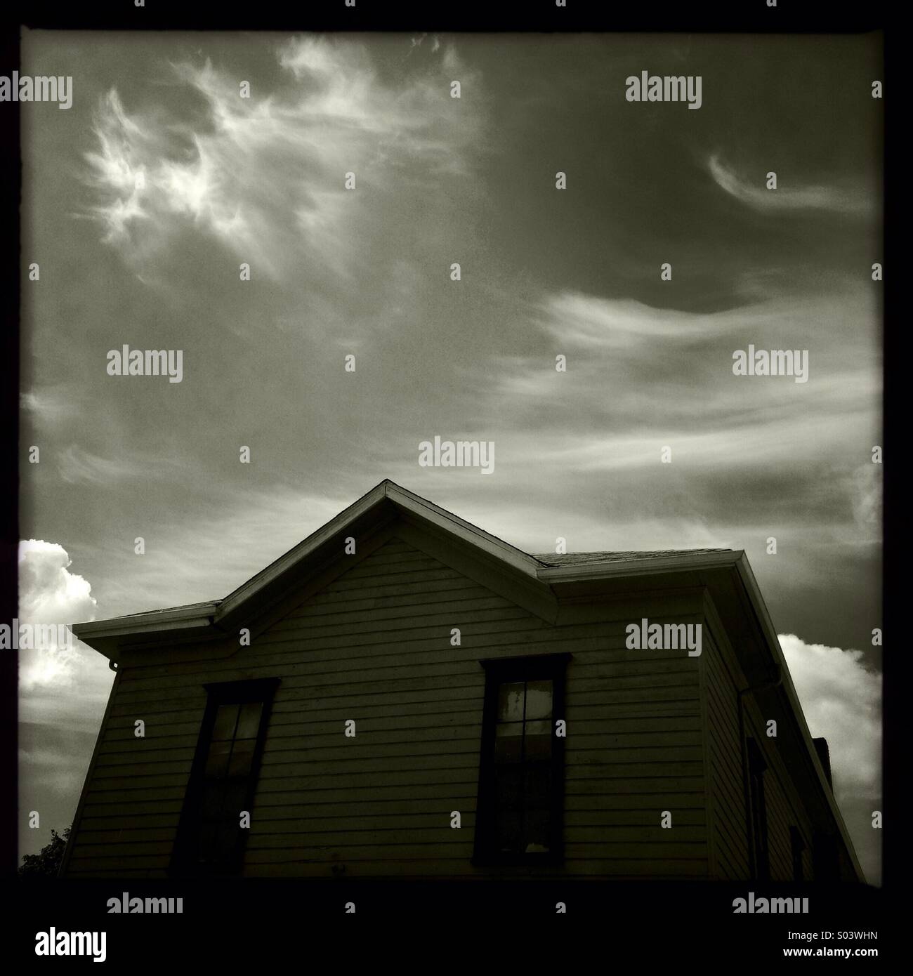 Black and white creepy looking building with dramatic clouds in the sky. - Stock Image