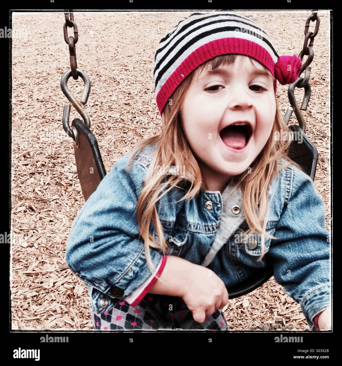 Toddler Caucasian girl having fun on a swing - Stock Image