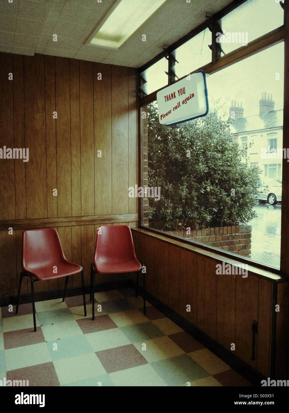 Retro style laundrette interior with red plastic waiting chairs. - Stock Image