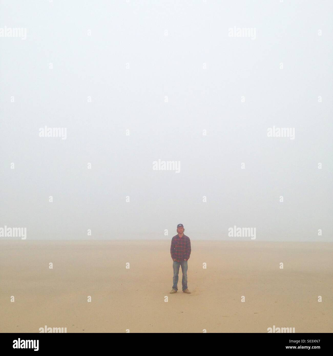 Portrait of a lone person standing on the beach in heavy sea mist. - Stock Image