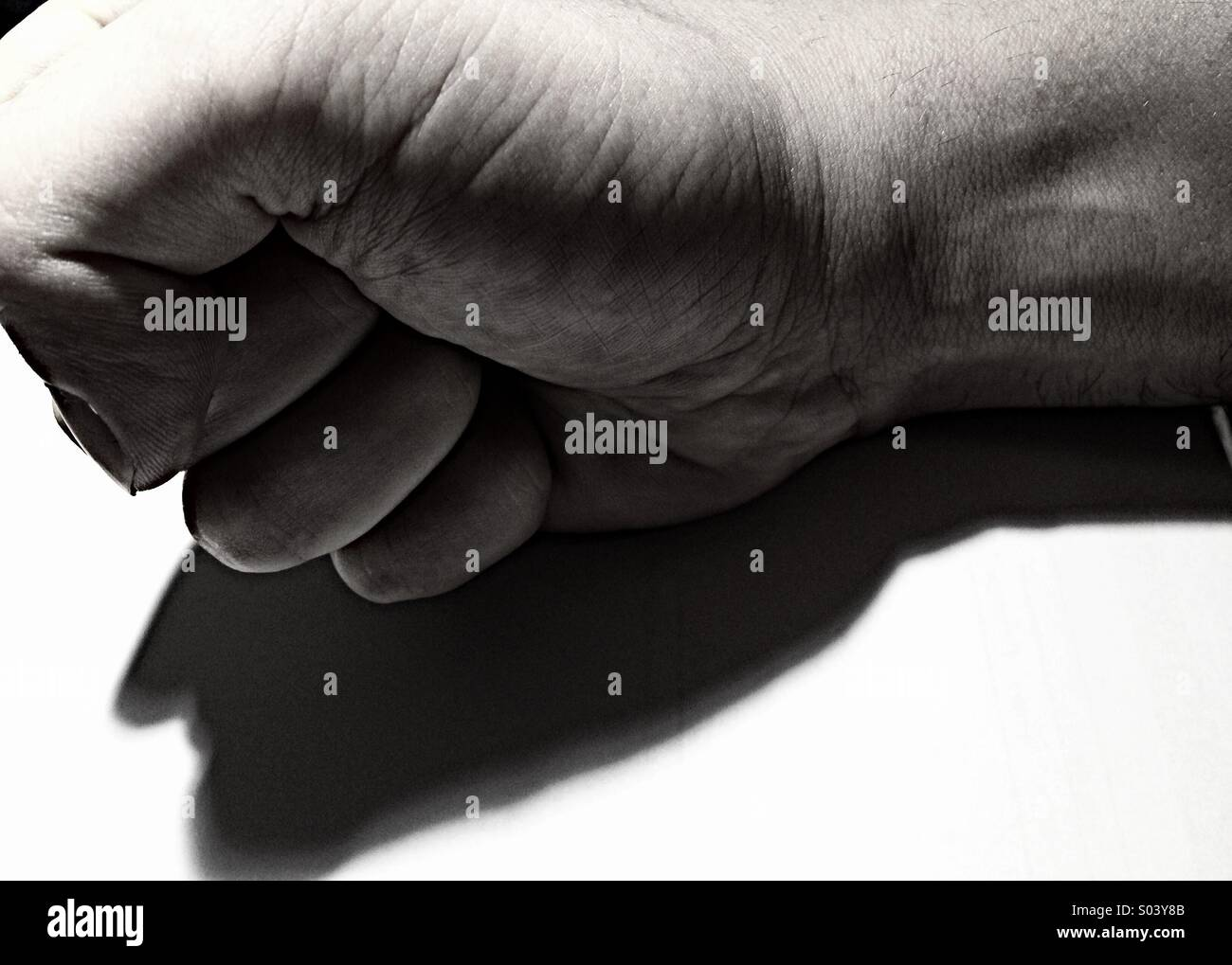 A closed fist symbolizing anger - Stock Image