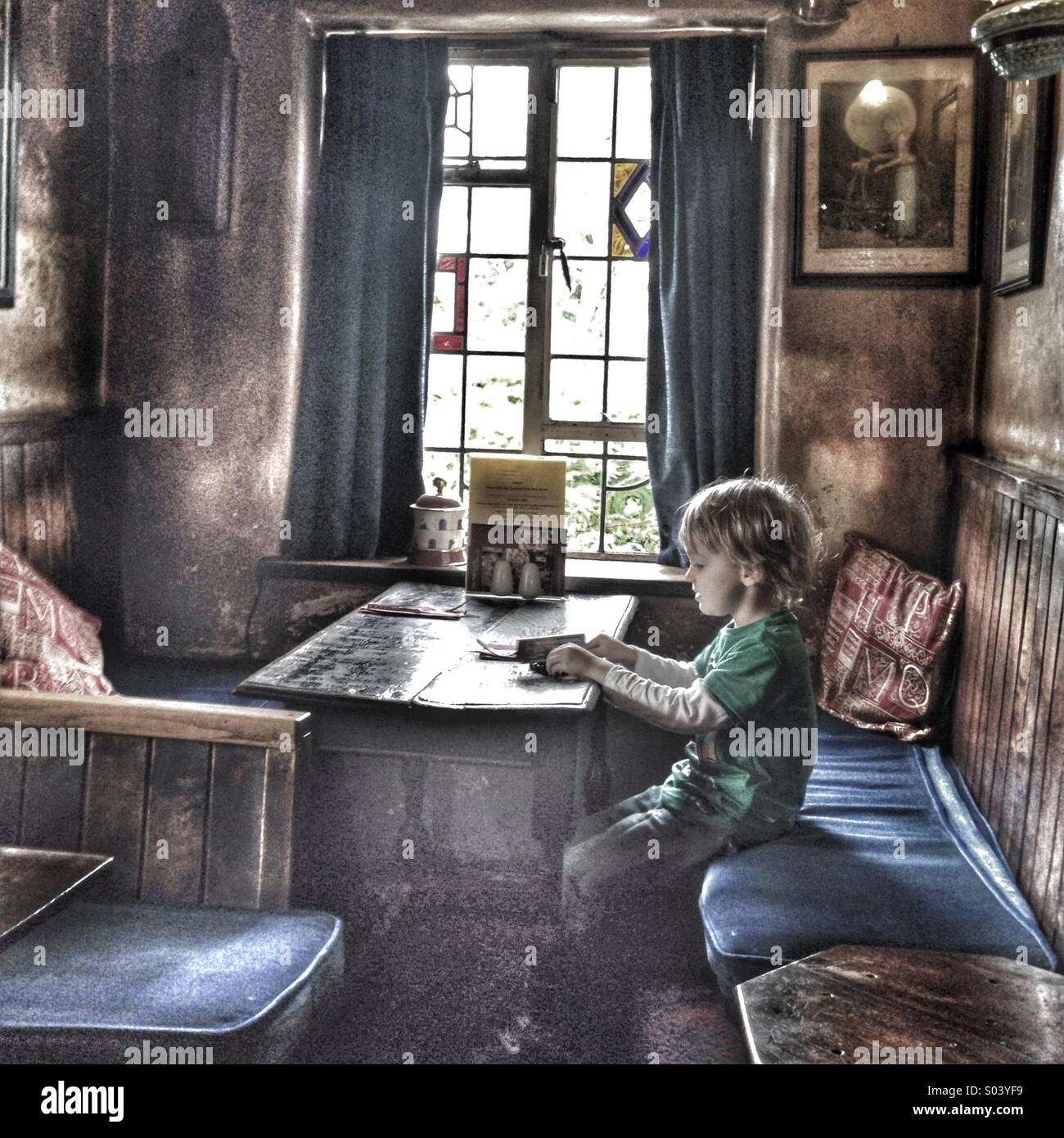 Boy sitting on his own at a table in an old pub - Stock Image