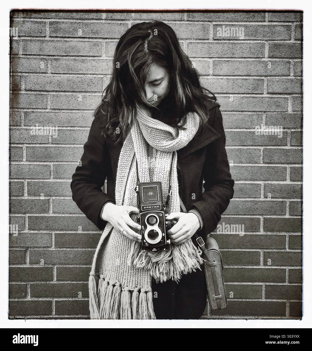 Young woman taking picture with vintage camera - Stock Image