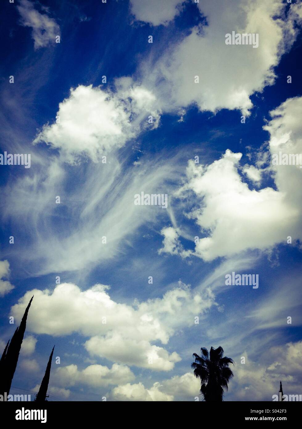White wispy and cumulus clouds in a blue sky - Stock Image