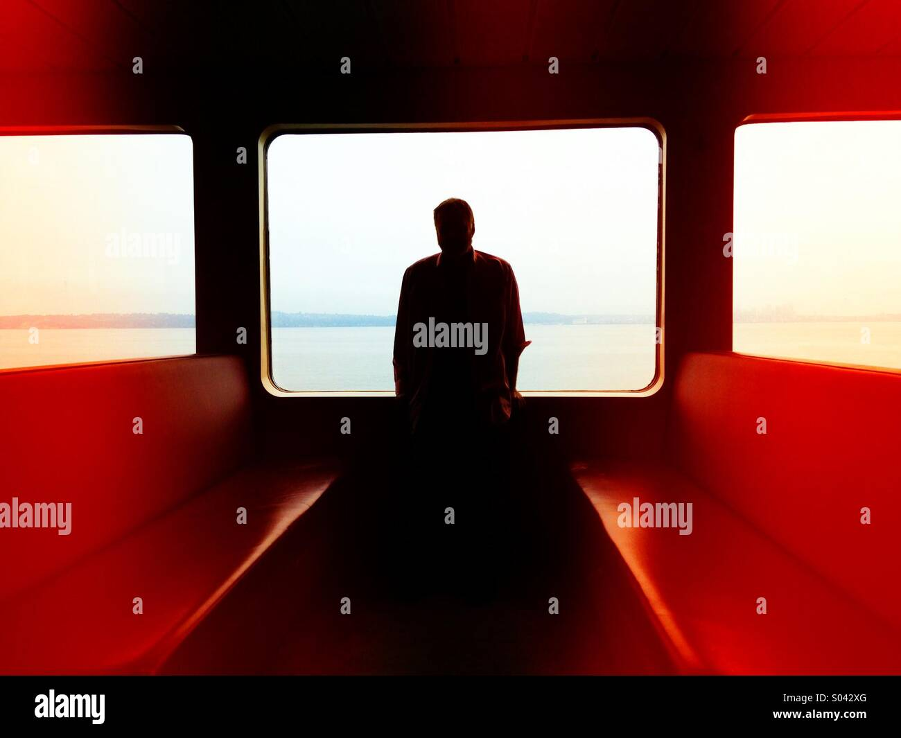 Silhouette of a man in the window of a ferry boat in Puget Sound - Stock Image