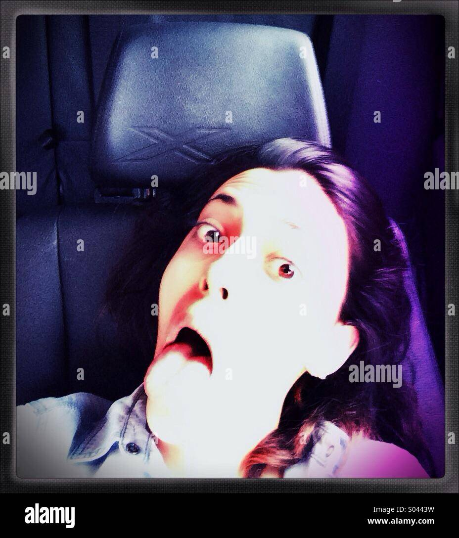 Frightened young woman in a car - Stock Image