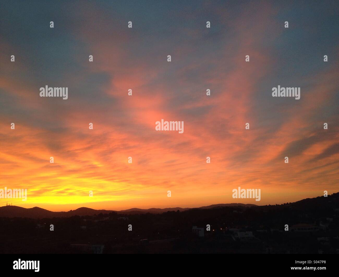 Ibiza sunset red, gold plumes. - Stock Image