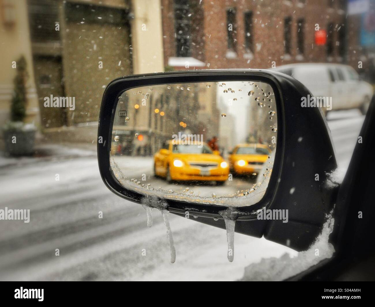 Looking into car rearview mirror at taxicabs on New York City Street on snowy day - Stock Image