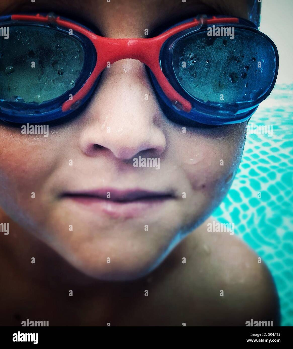 A happy smiling boy in a swimming pool - Stock Image