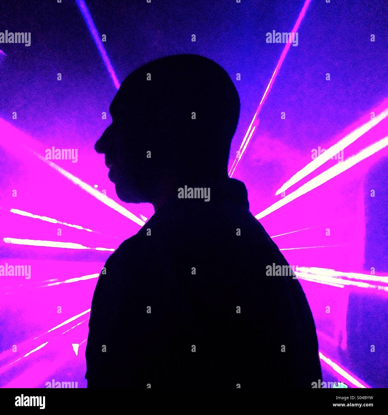 Man silhouetted in purple pink laser in nightclub - Stock Image