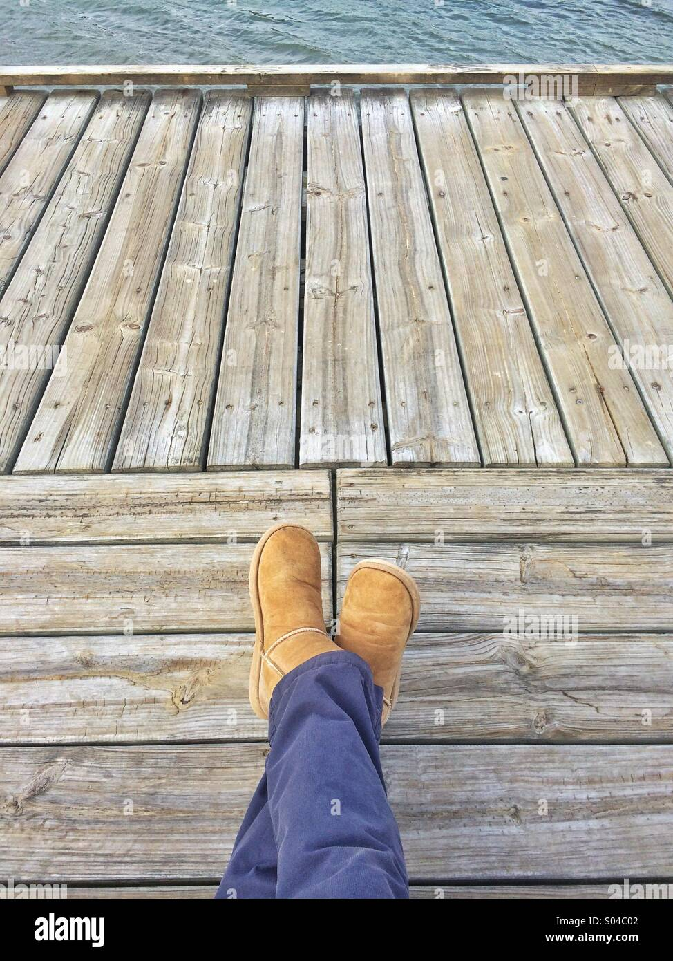 Relaxed legs crossed on wood deck looking towards Water - Stock Image