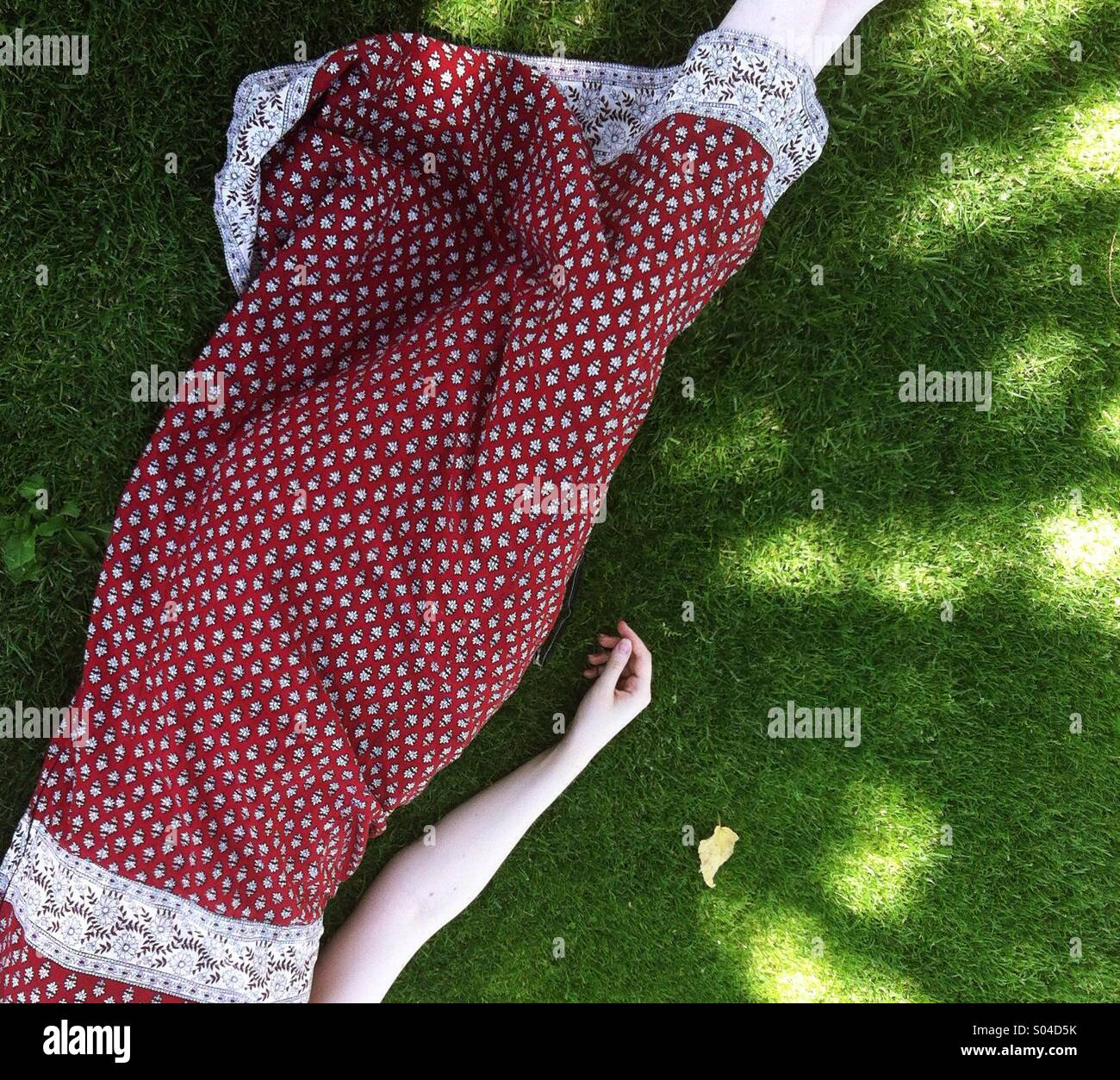 A young woman in a red patterned dress lies daydreaming beneath the shadows of trees, beside a single fallen leaf, - Stock Image