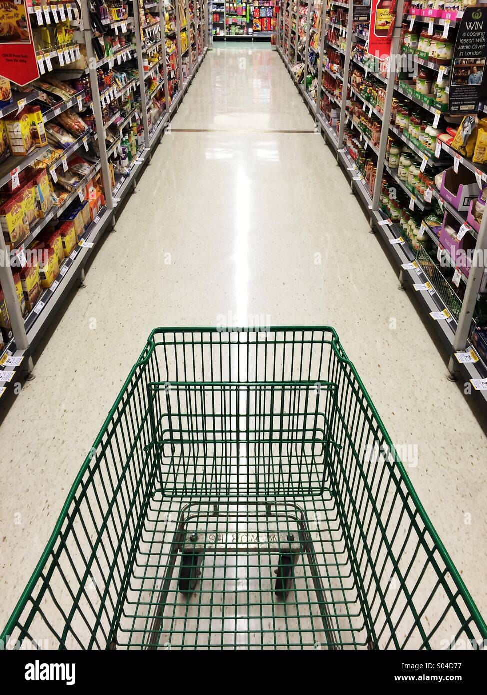 Empty shopping trolley in a passageway in a shop - Stock Image