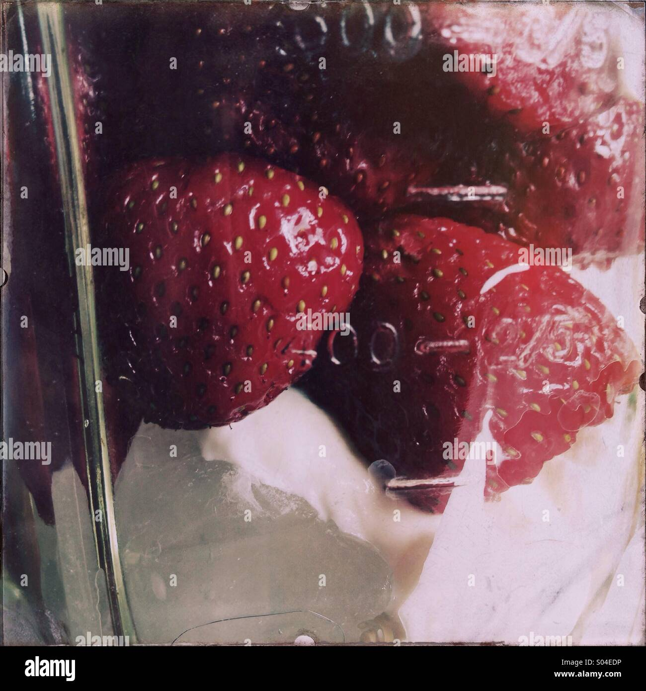 Strawberries are seen in a blender for making a smoothie. - Stock Image