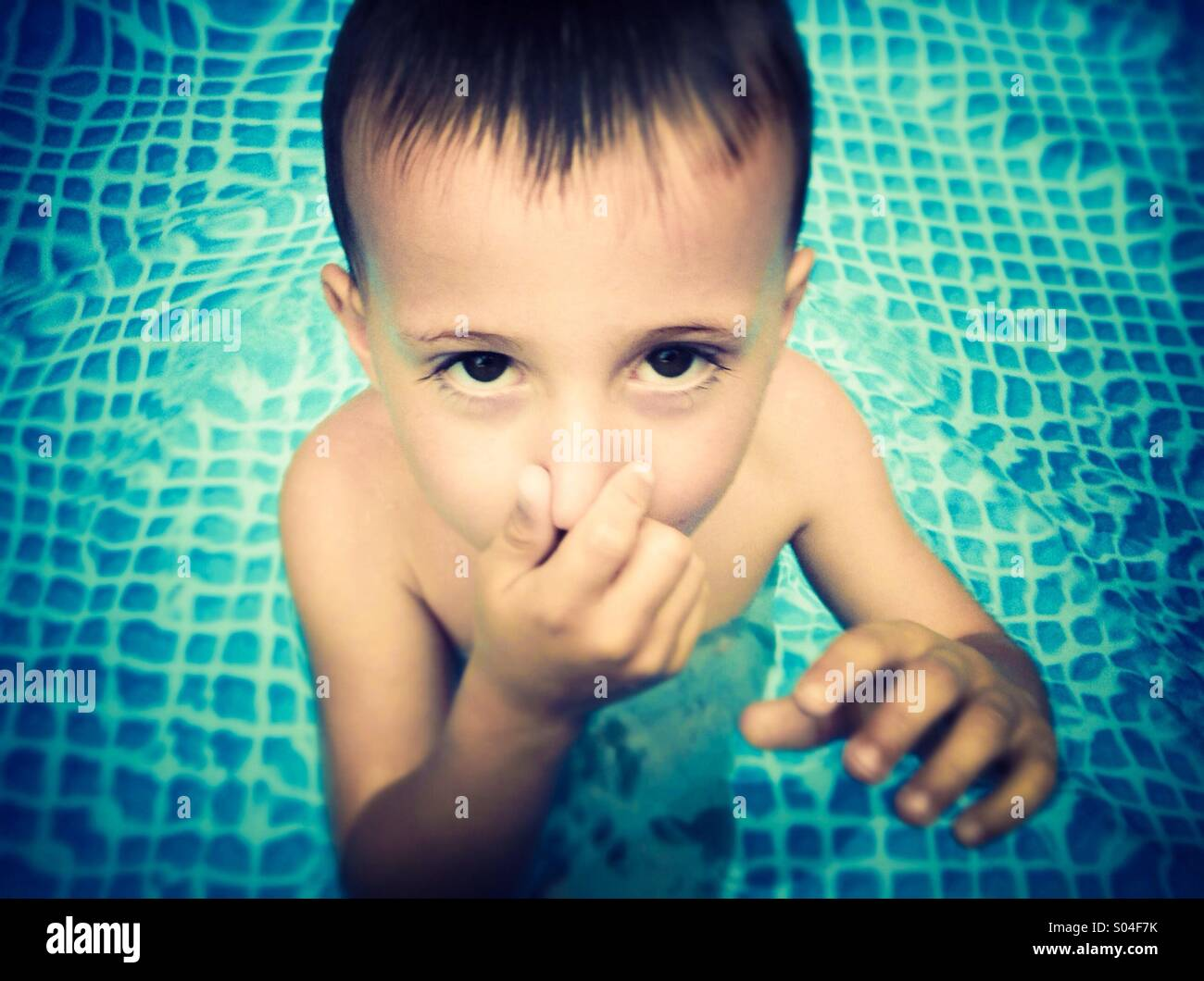 Boy pinch his nose in a swimming pool Stock Photo