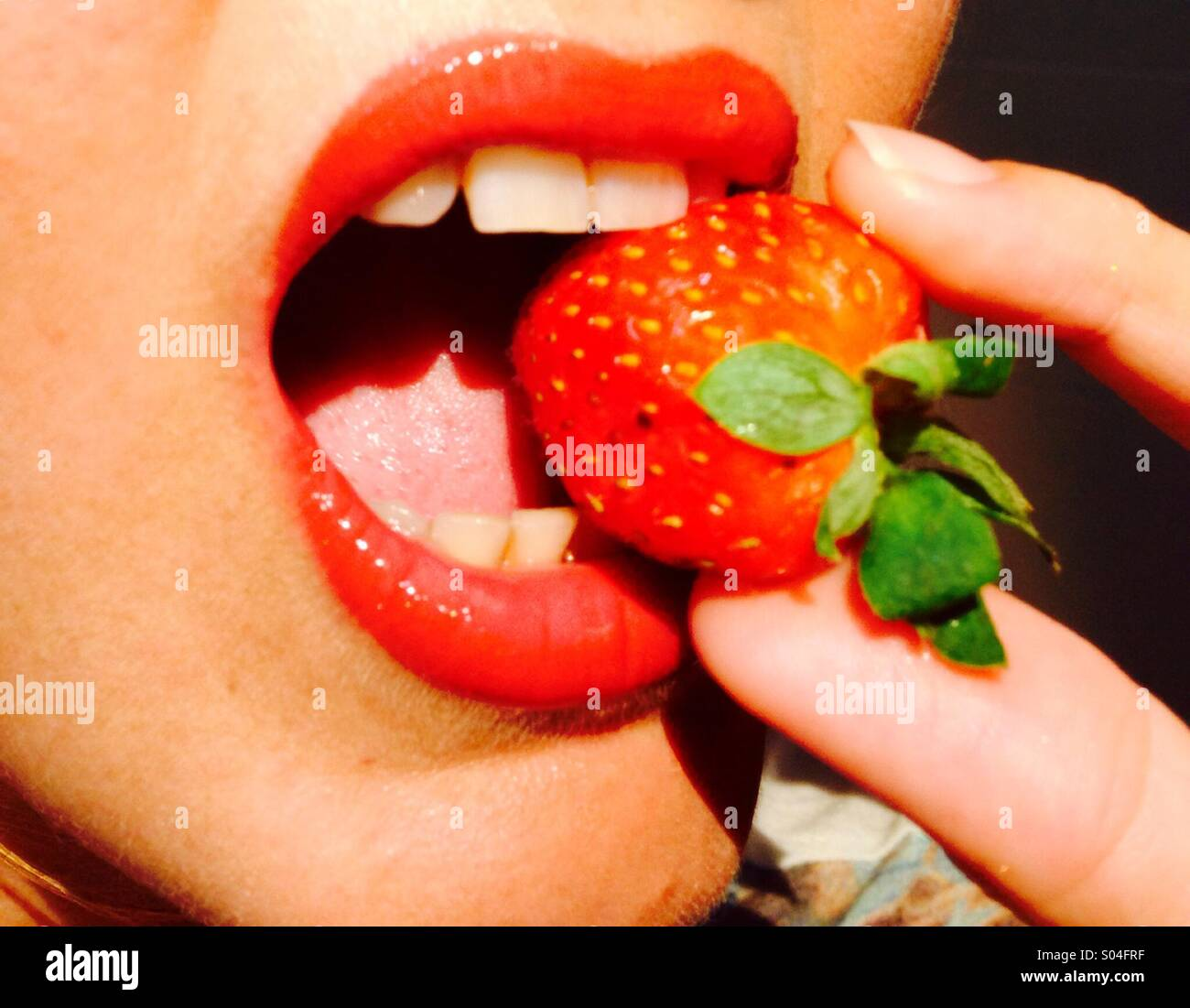 Strawberry being bitten between red lips - Stock Image