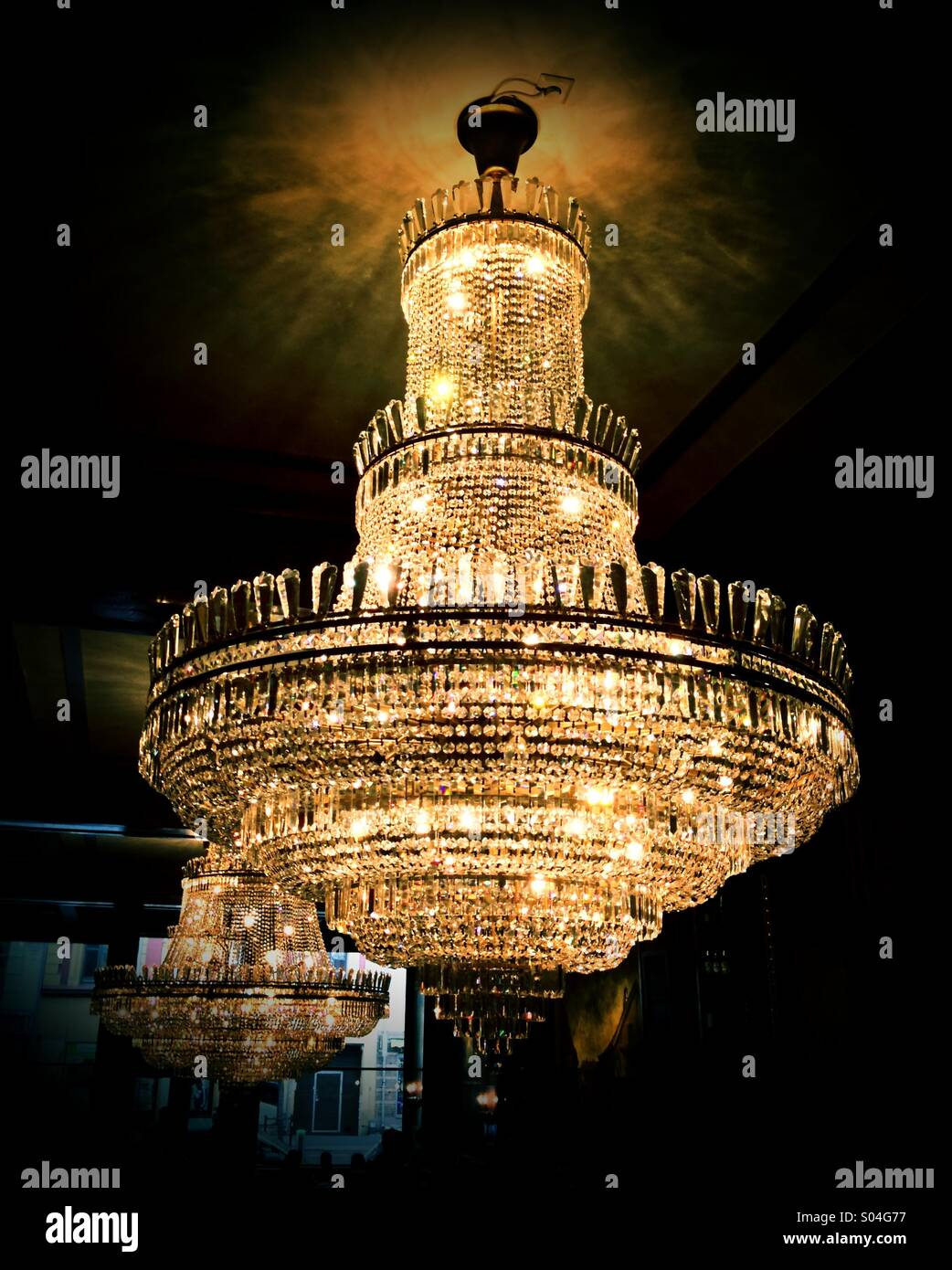 Antique chandelier in a night club and restaurant which was once very grand and lavish. - Stock Image