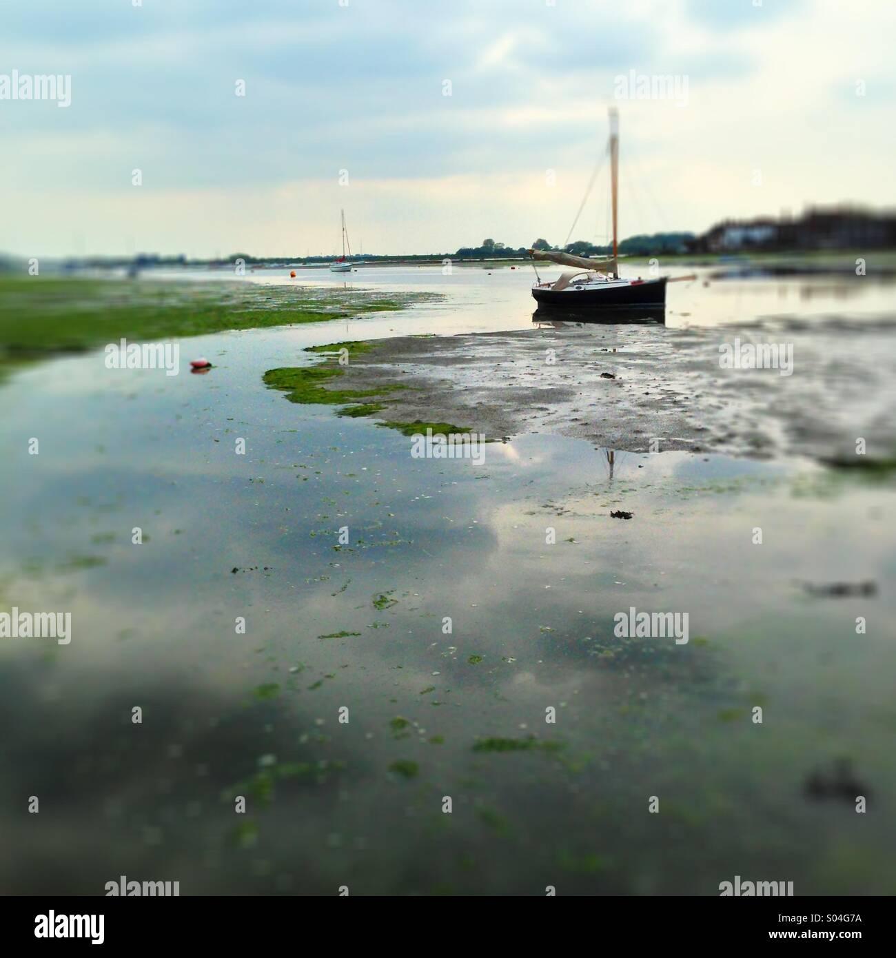 Sailing boat at low tide in tidal estuary. Stock Photo