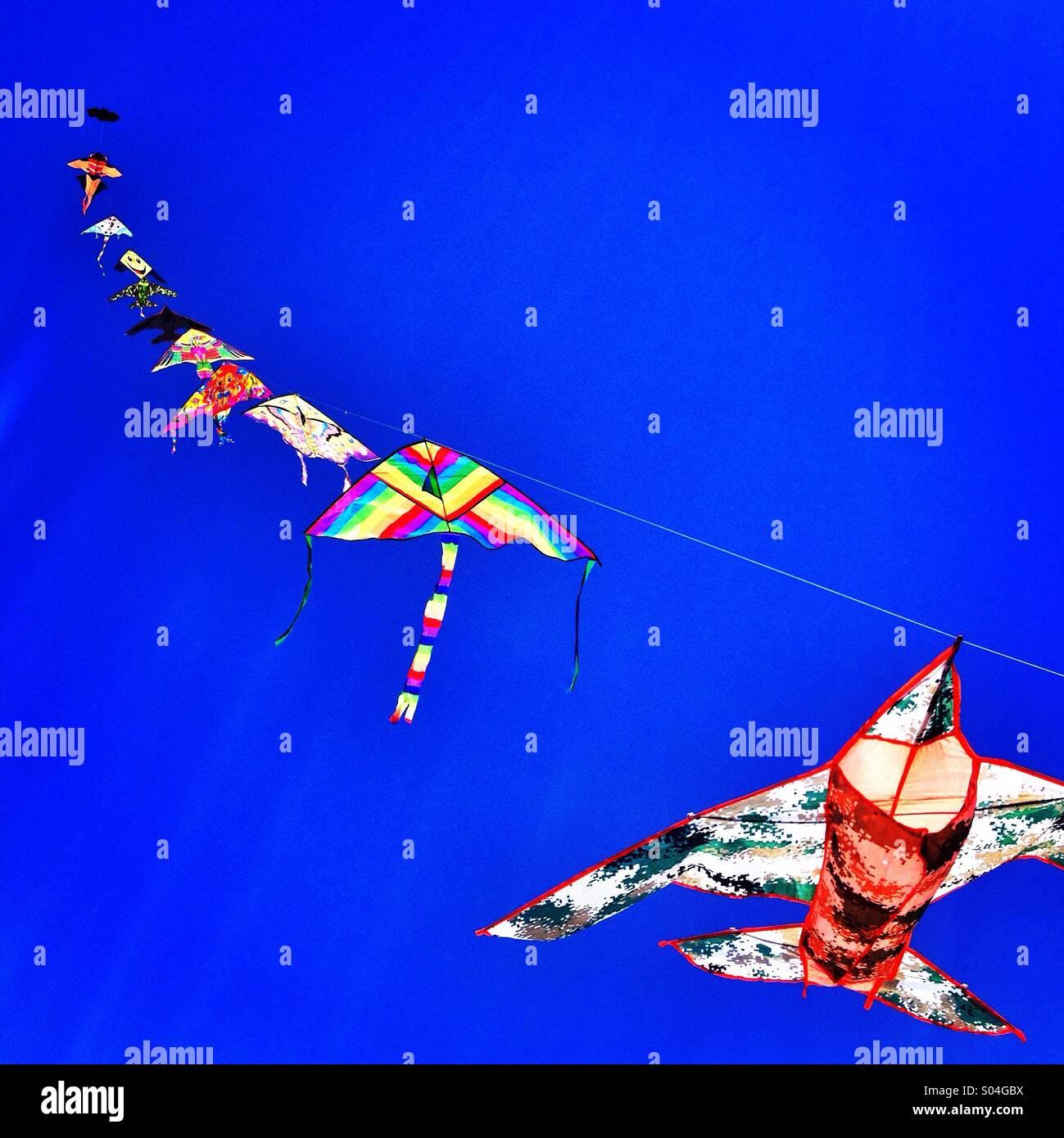 Children flying kites and blue sky - Stock Image