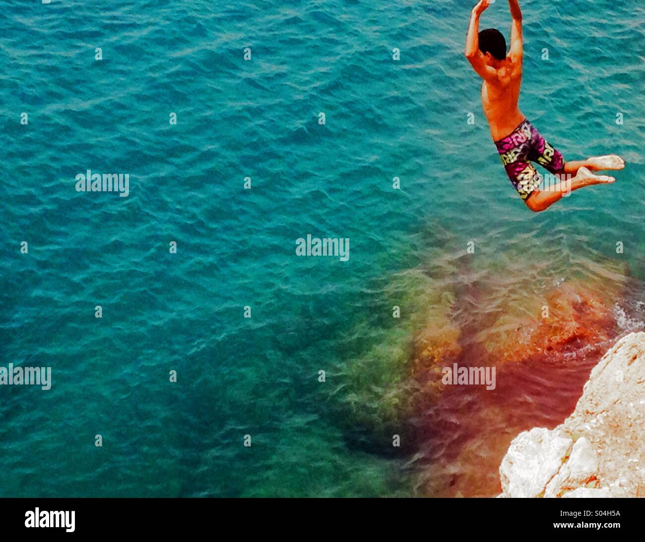 Boy leaping off a cliff into the sea - Stock Image