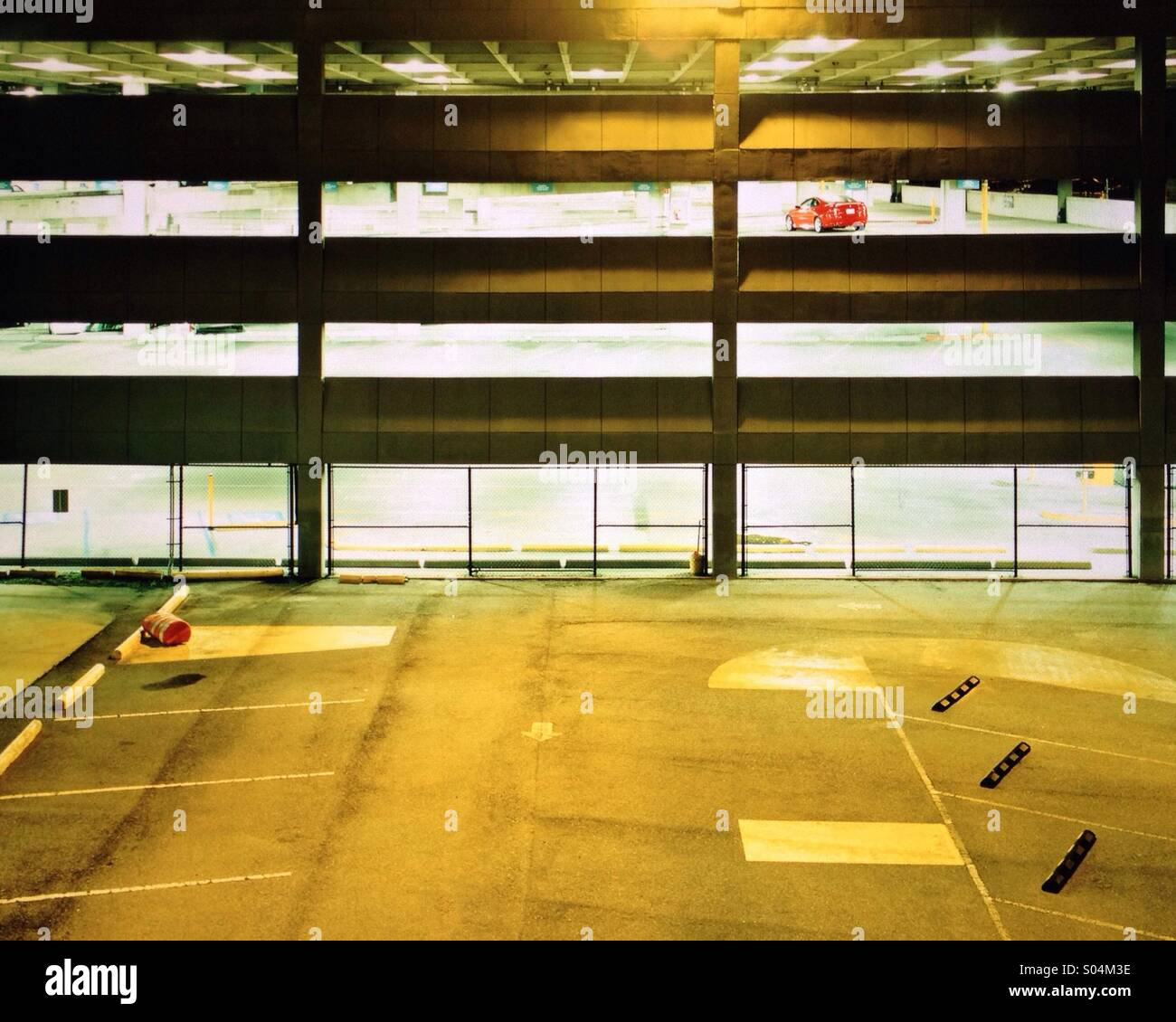 Red car in empty parking garage - Stock Image