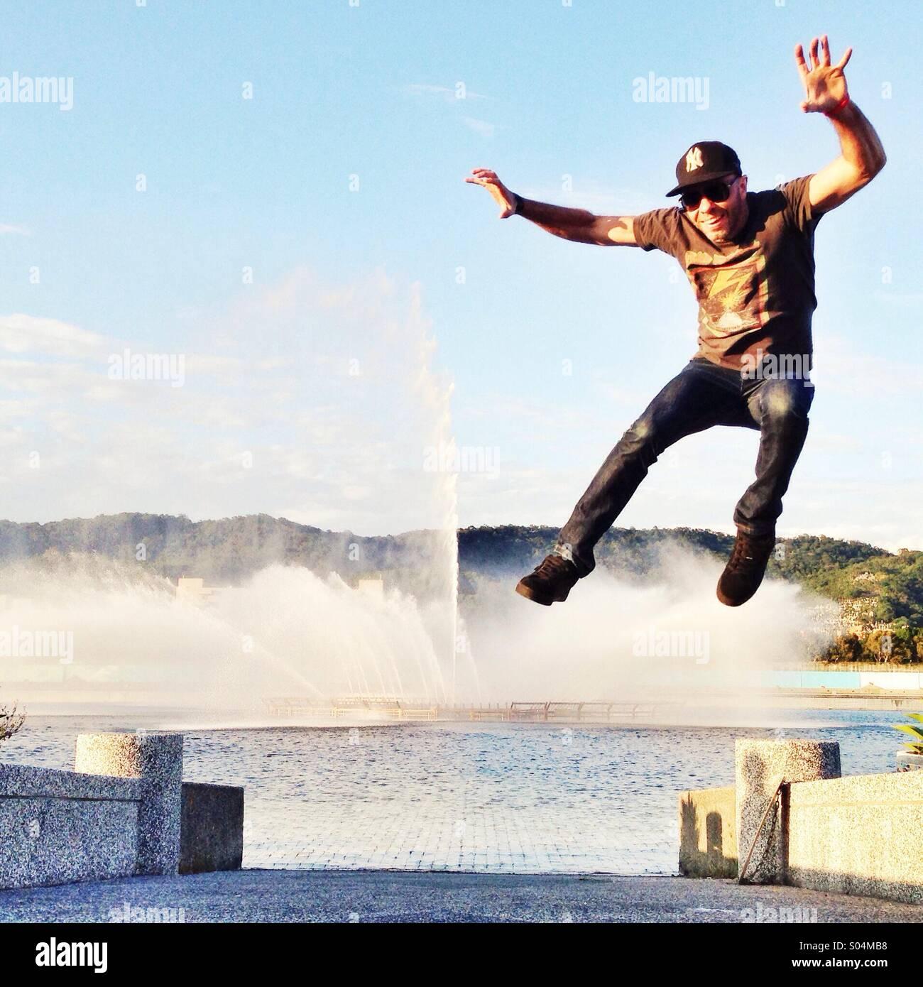 Jumping in Taipei Taiwan lake fountain. - Stock Image