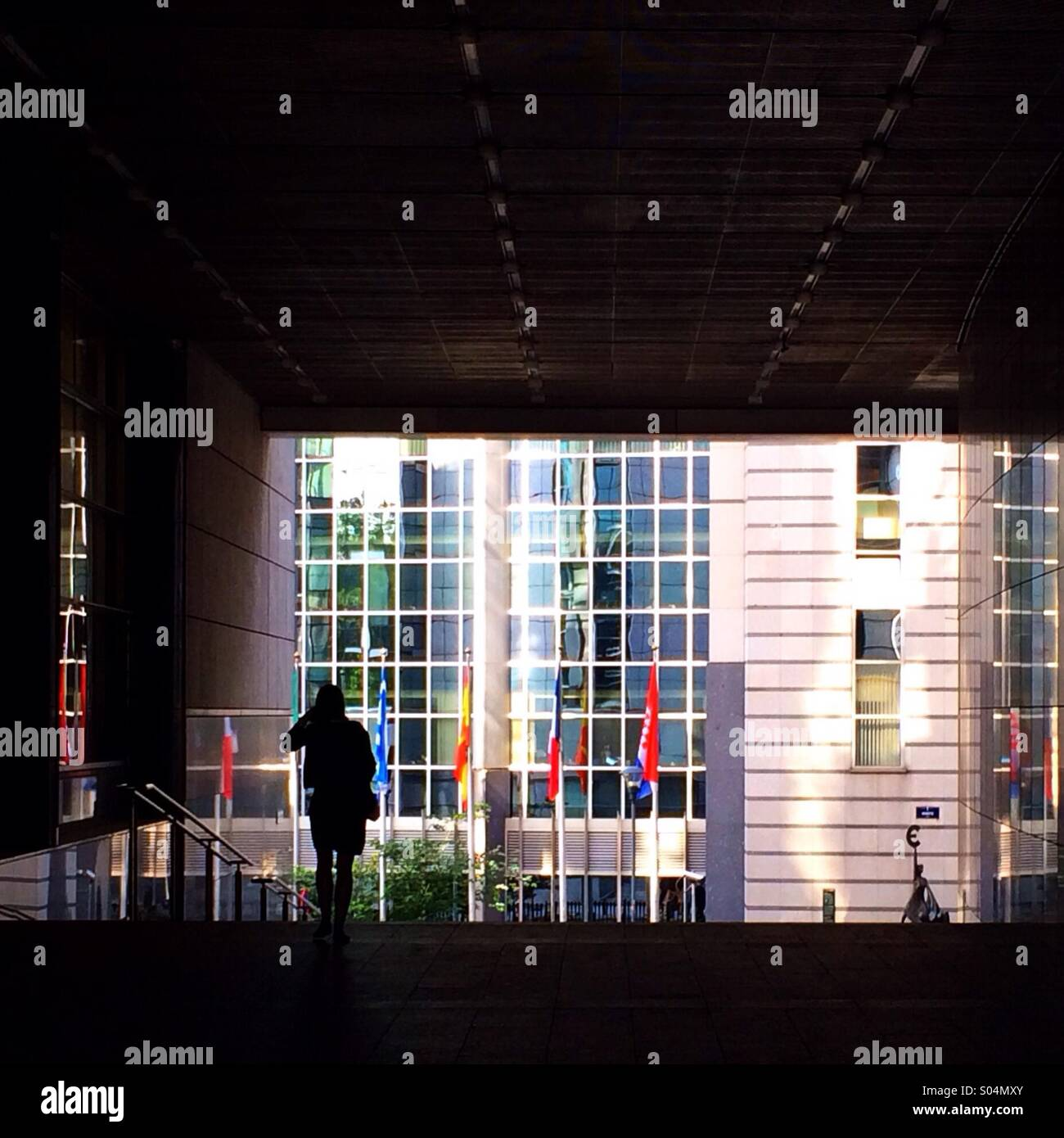 Silhouetted figure outside European Parliament building, Brussels - Stock Image