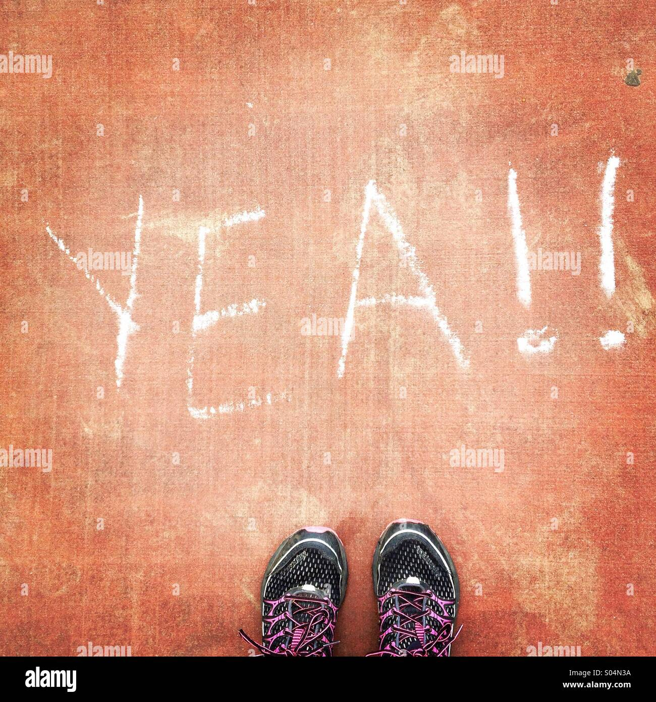 Inspirational chalk message 'yea!' with tennis shoes - Stock Image