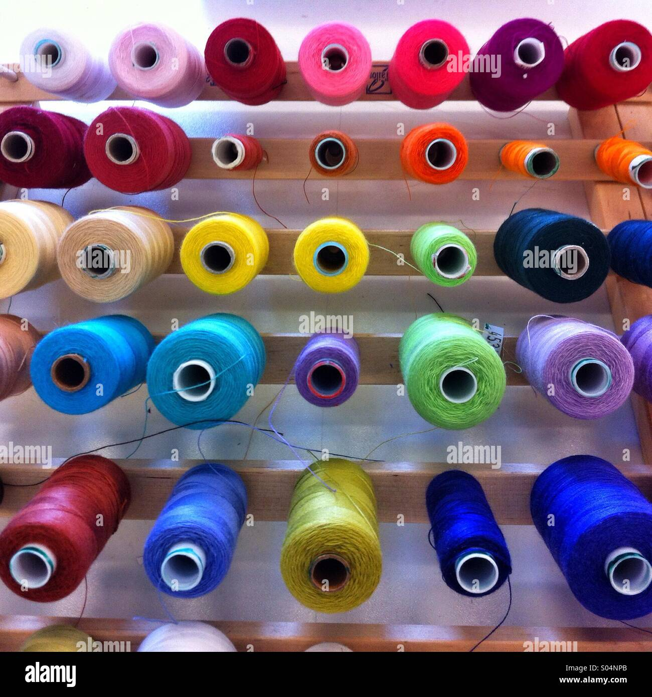 Reels of coloured cotton threads on a wooden rack - Stock Image