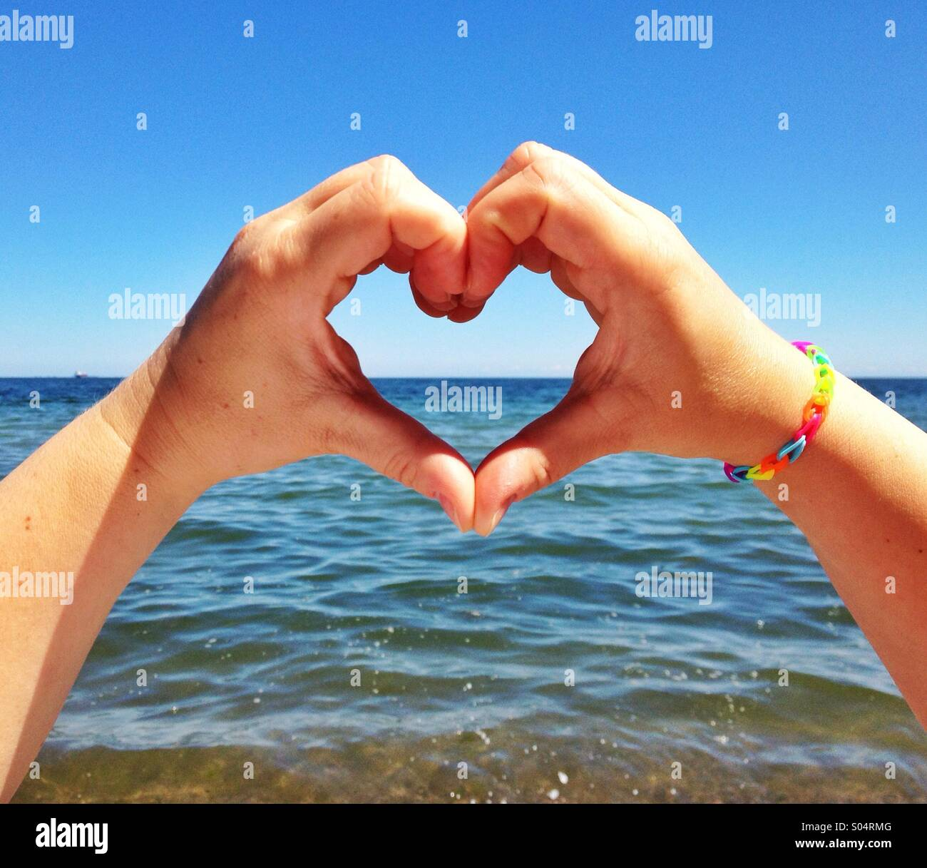 Hands heart shape against the sea - Stock Image