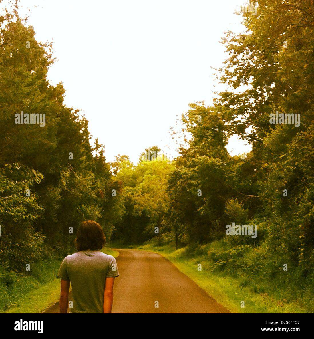 A young man walks down a narrow lane surrounded by trees. - Stock Image