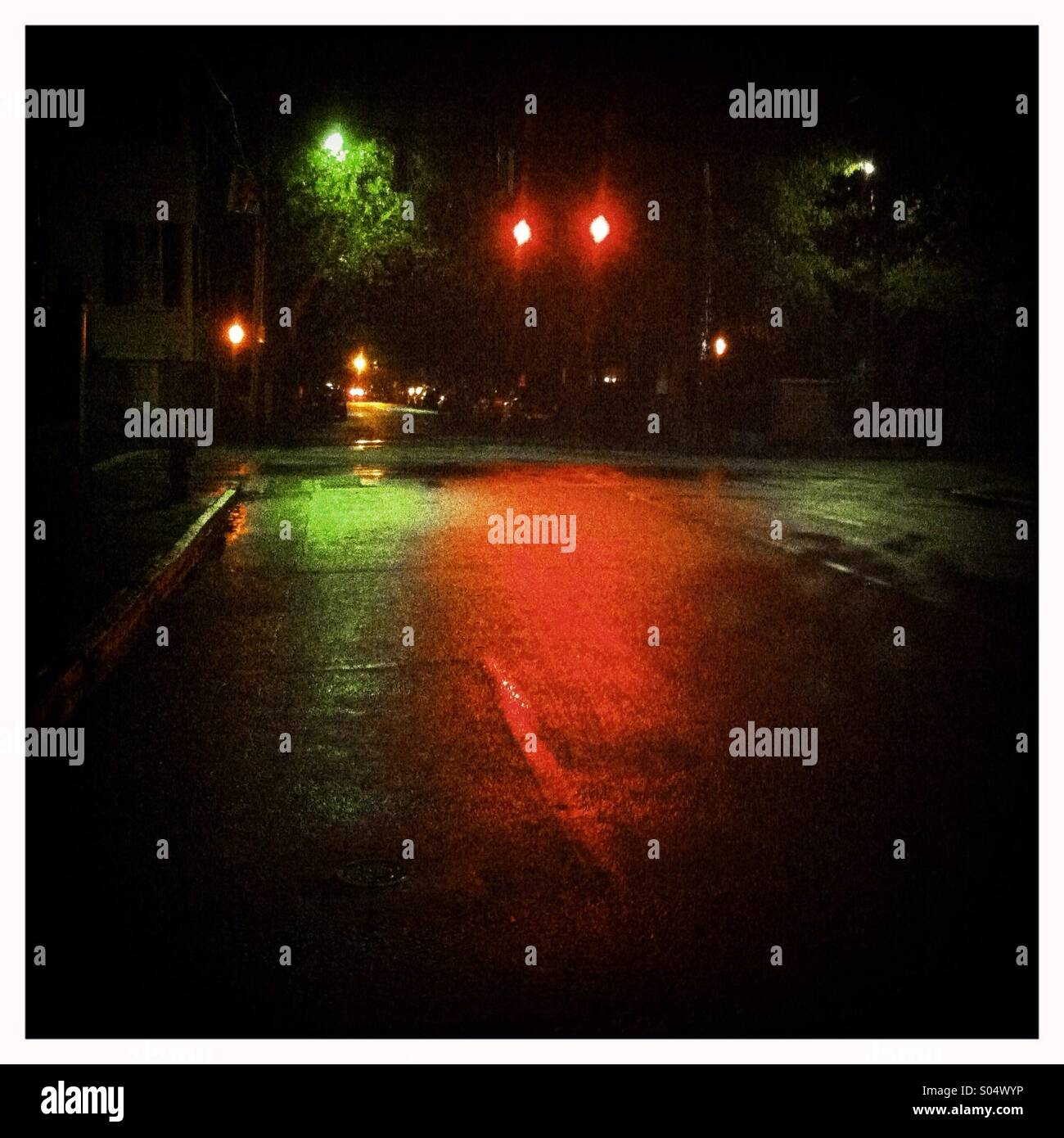 Red and green lights reflected in a wet city street - Stock Image