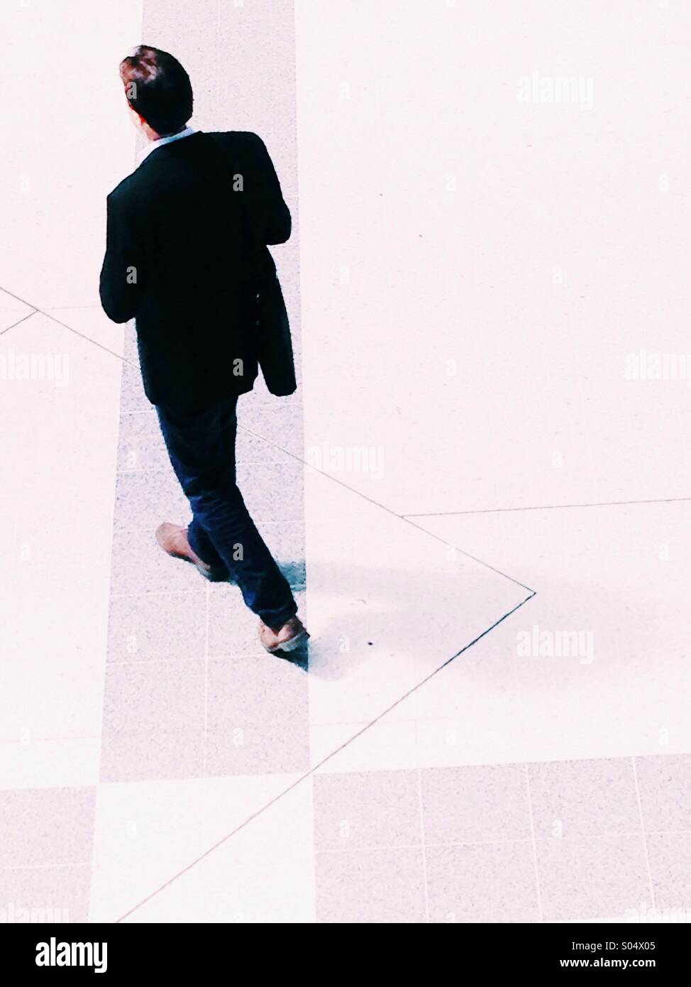 Businessman in a black suit walking seen from above - Stock Image