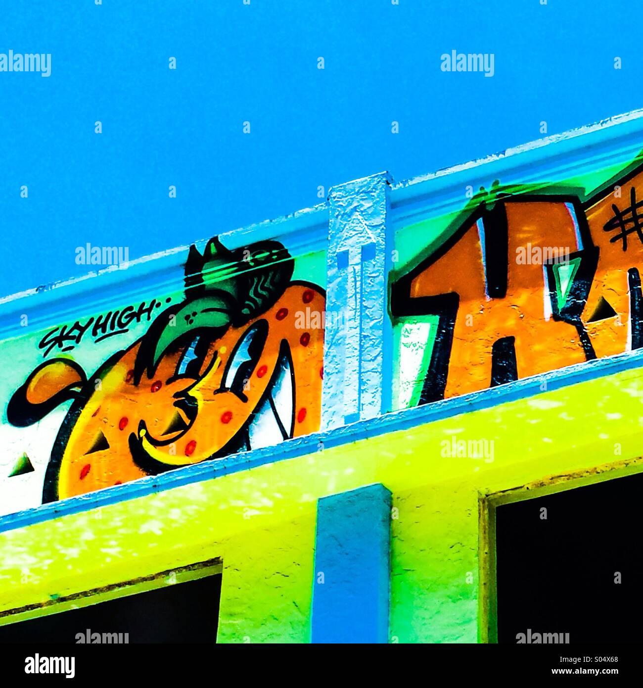Vibrant graffiti decorates facade of old historic Miami building. - Stock Image