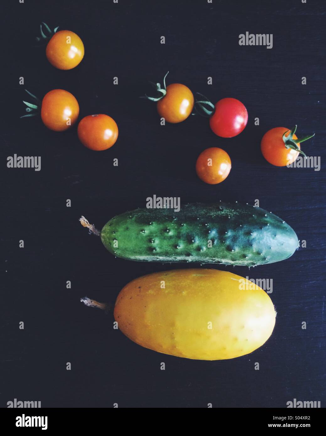 Tomatoes and cucumbers harvested from a garden. - Stock Image