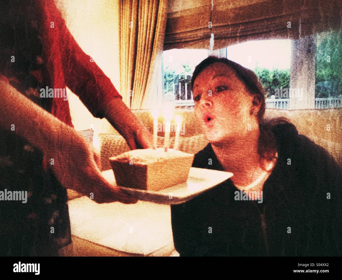 Woman blowing out candles on a small birthday cake - Stock Image
