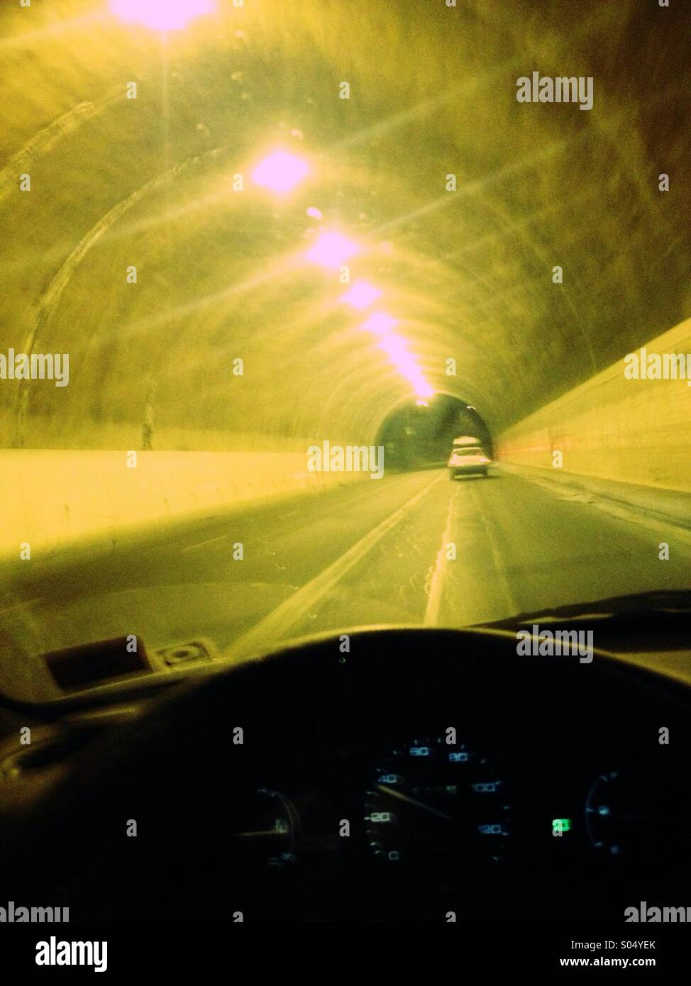 Driver's eye view of car going through a long tunnel at night. - Stock Image