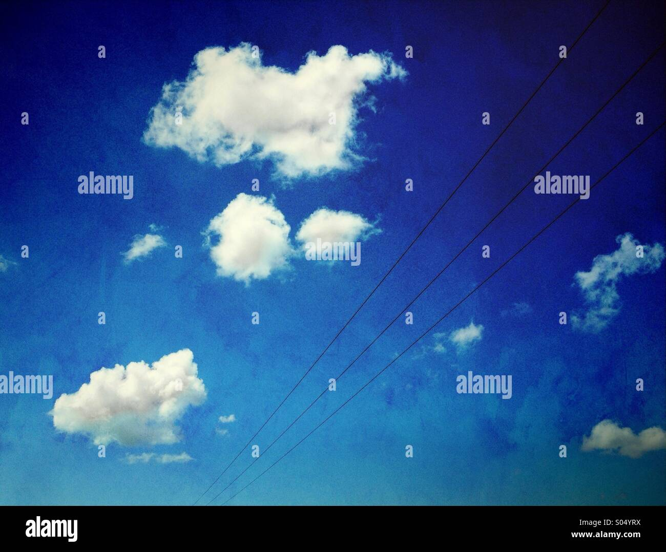Pylon wires and white clouds against blue sky - Stock Image