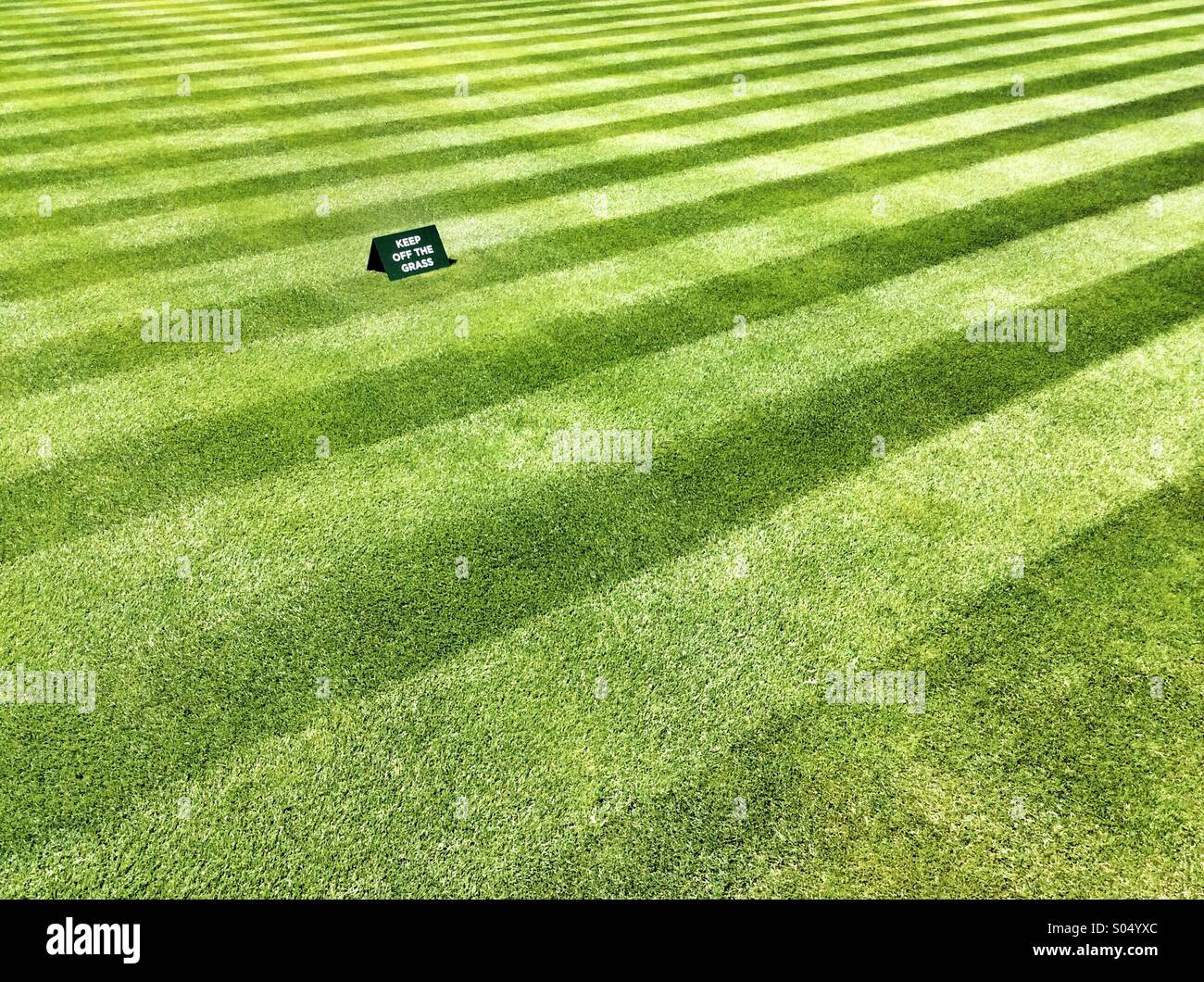 Perfectly mown grass lawn with stripes and keep of the grass sign - Stock Image