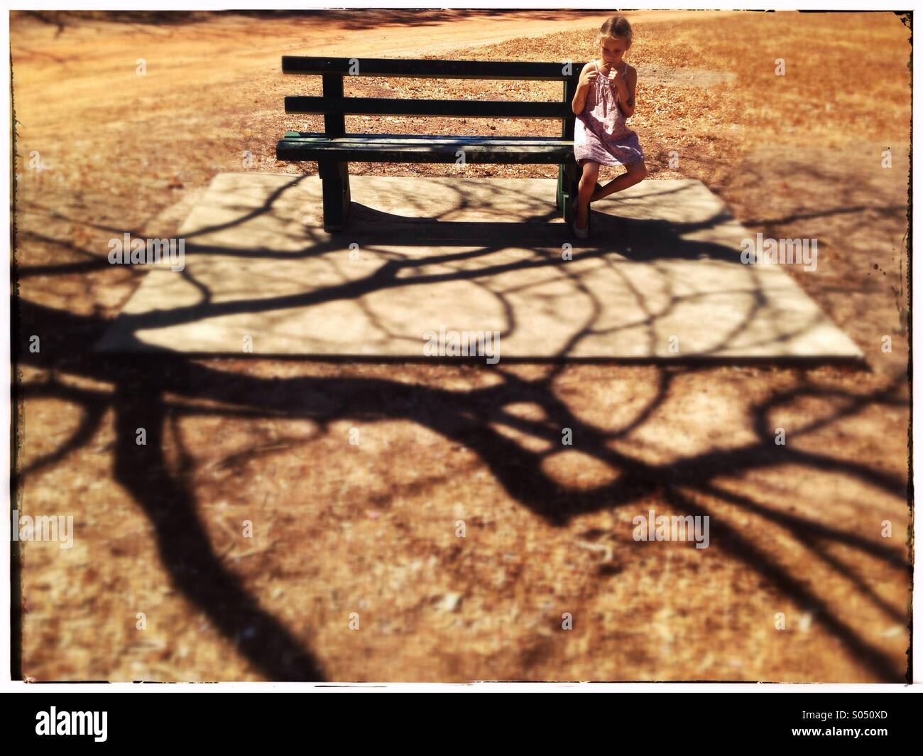 Little girl on a park bench. - Stock Image