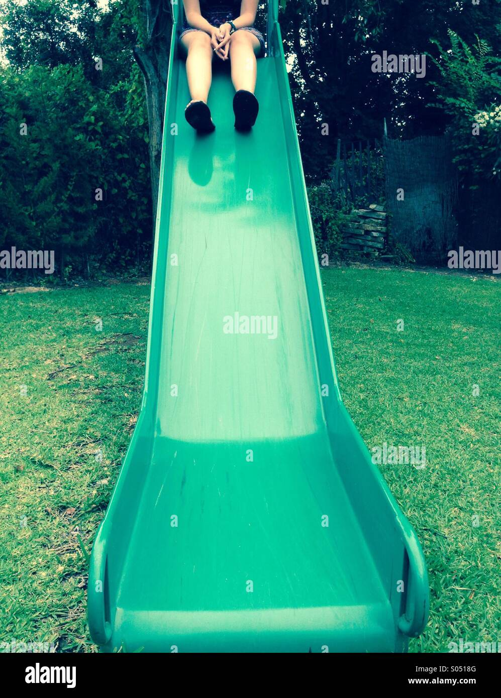 Young woman at top of the slide - Stock Image