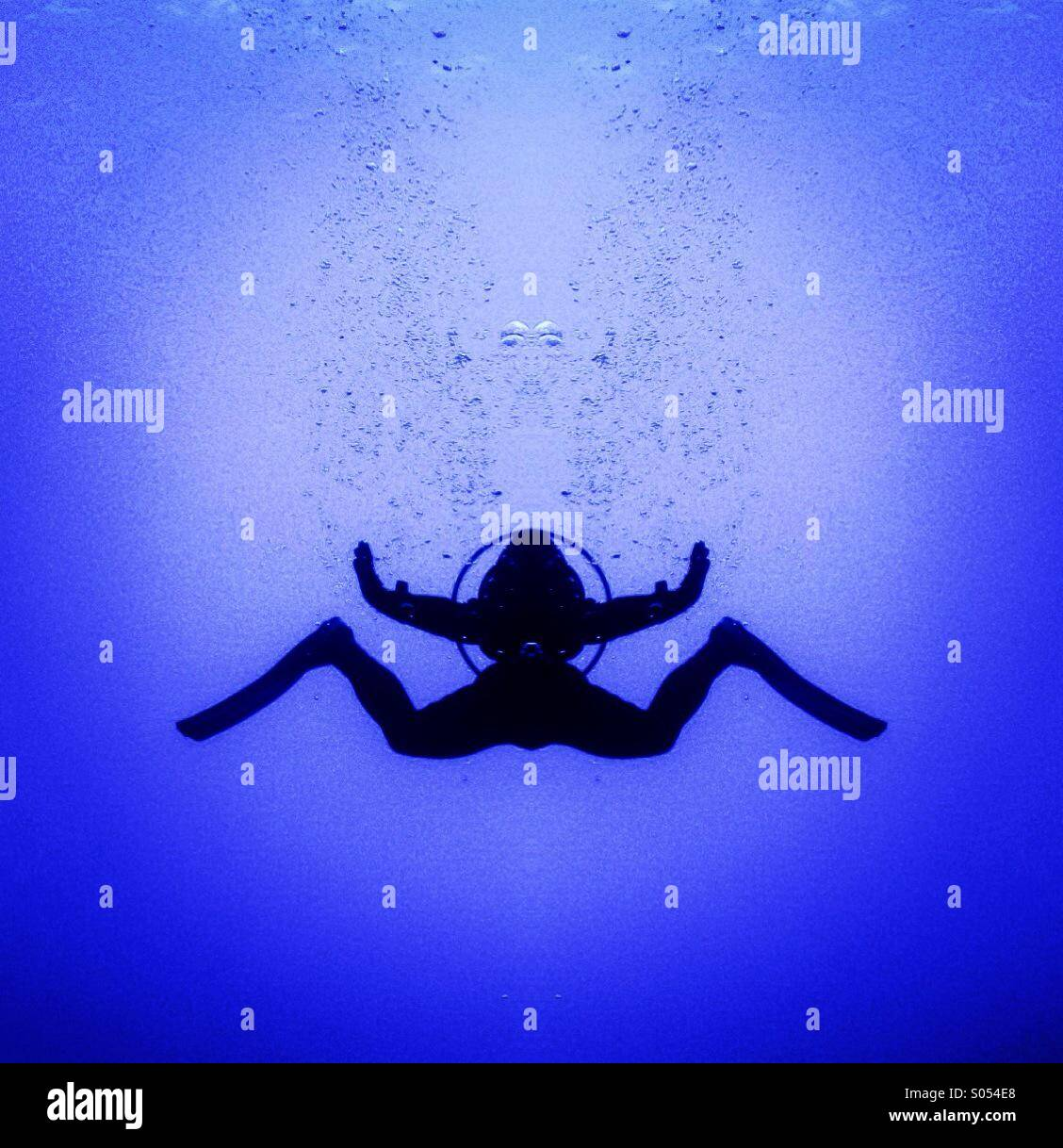 Scuba diver silhouette mirrored in mid water. - Stock Image