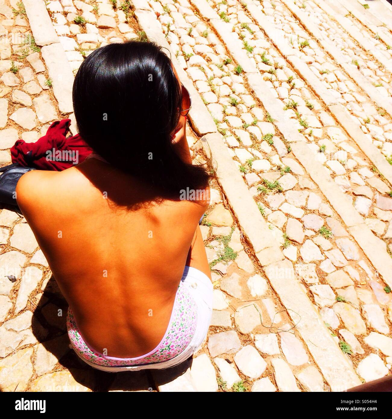 Girl sitting on stone steps, Portugal - Stock Image