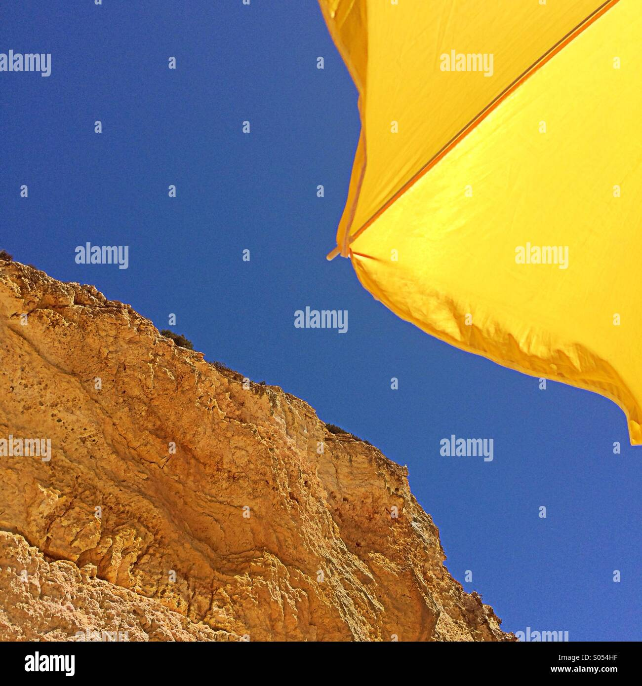 Yellow parasol, blue sky and rocks, Algarve, Portugal - Stock Image