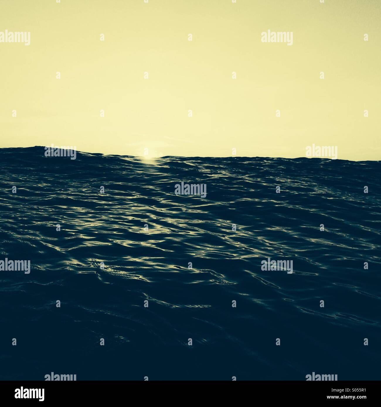 First light in the ocean as the sun appears on the horizon - Stock Image