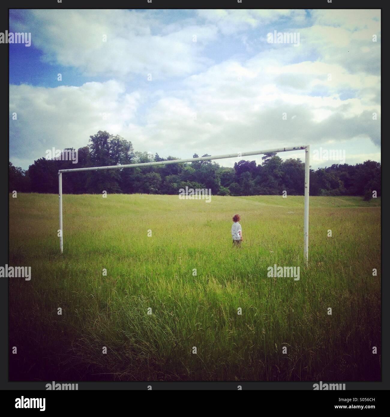 Lone boy stood between goalposts overgrown field - Stock Image